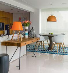 Casal muda-se para um apartamento de 180 m² próximo à casa dos filhos. Projeto do escritório InHouse Designers l O piso de limestone dá unidade à sala, que tem espaço generoso para a circulação. Sobre o aparador Arthur Casas, da Micasa, abajur de Fernando Prado para Lumini.