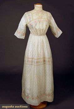 "PASTEL EMBROIDERED ARTS & CRAFTS DRESS, 1913 Handkerchief linen hand embroidered w/ blue dot ground & stylized rose bands, handmade bobbin lace trim, silk cord & tassel belt, center back closure, B 38"", W 25"", L 55"", (few faint small stains) excellent."