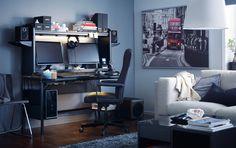 Uma secretária preta com espaço para dois ecrãs, colunas e arrumação por cima, numa sala.