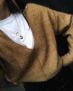 Accumulation de colliers dorés + tee-shirt blanc + pull camel grand col V = le bon mix (photo Darja Barannik)