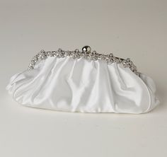 The White Satin Clutch with Rhinestone Flowers is perfect for the bride on her wedding day.  Cream satin bag has a floral silver-plated design along the top and can be used as a clutch or over the shoulder bag.