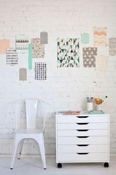 Parede de tijolos a vista pintada de branco com pequenos recortes de gravuras abstratas e geométricas