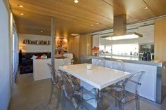 Cocina, salón y comedor. integrados en un mismo espacio. La madera, el blanco y las #sillas transparentes de #kartell acaparan nuestras miradas | Fotografía de © Matías Pérez Illeras