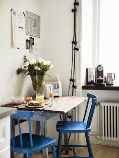 Love these bright blue chairs in this small but functional French kitchen