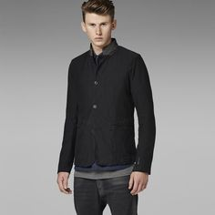 4-button blazer with large hand-pockets and  a rounded hem that is slightly longer in the front.