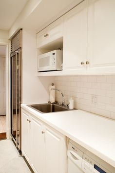 Long laundry room features white cabinets paired with white countertops and subway tiled backsplash.