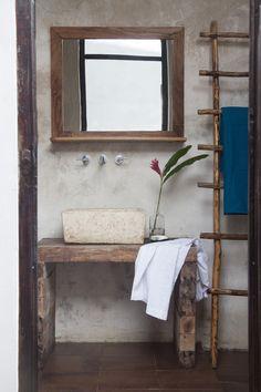 reforma baño rústico con lavabo de piedra sobre mueble de madera reutilizada, grifos de pared, escalera como toallero.
