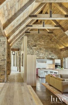 Meant to evoke an updated old  farm building, the great room,  which includes the kitchen and  living area, features curated  stone walls and a dramatic  gabled ceiling highlighted by  fir trusses. A hallway leads to  the media room.