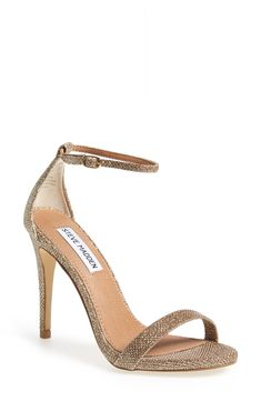 A slim ankle strap lends a dash of on-trend elegance to this gold sparkly high-heel sandal.