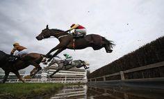 Tom O'Brien riding Sandy Beach (C, red/yellow) clear the water jump before winning The bet365 Handicap Steeple Chase at Newbury Racecourse on November 3, 2016 in Newbury, England. (Photo by Alan Crowhurst/Getty Images)