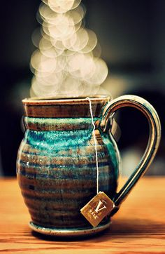 happy bokeh tea in a blue and brown glazed pottery mug