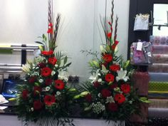 Made by me. Two red and white front facing pedestal arrangements containing gladioli, white lillies, red germini, red roses and lizzy.