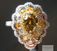 the platinum hand forged shank is set with natural fancy colored diamonds.