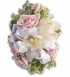 """Light pink spray roses with white dendrobium orchids, seeded eucalyptus and variegated pittosporum.    Approximately 6 1/2"""" W x 5"""" H."""