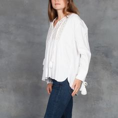 Bohemian lightweight tunic top eased by dropped shoulders and soft shirring at the bust line and back yoke. Braided-rope tassels tie at neckline and cuffs. Hidden hook-and-eye closure.Split neckline.Bracelet sleeves.80% Tencel lyocell, 20% cotton with 100% cotton contrast.