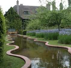 Bryans Ground, Herefordshire, UK. Arts & Crafts house and garden of Horticultural journalists David Wheeler & Simon Dorrell... Serpentine rill through orchard underplanted with Iris sibirica.