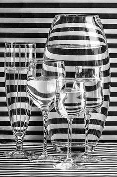 ALL LINED UP AND READY BY MAGGIE TERLECKI  is an experiment showing how light bends through glass. The refraction bends the light and skews what you see through the wine glasses and vase. This black and white image is also very modern and will look amazing on your walls. CLICK IMAGE FOR MORE INFORMATION. #stilllifephotography #fineartphotography #blackandwhitephotography #maggieterlecki #refraction #glass #wineglasses
