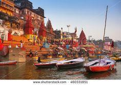 Varanasi, India - February 06, 2014: Boats at river Ganga and people at holy ghats among ancient hindu temples in the early morning in Varanasi, or ancient Benares city, India