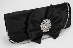 Ruched satin, bow and diamante detail to the front. Plain to the back. Lined with an inner pocket. 2 detachable chains measuring and Magnet closure. Size (cm): 26 wide x 10 high x 4 deep Black Clutch Bags, Designer Leather Handbags, Crystal Flower, Black Crystals, Black Satin, Laptop Bag, Evening Bags, Jewelry Stores, Classic Style