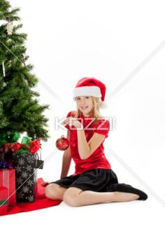 smiling girl holding christmas bauble. - Portrait of a smiling girl holding christmas bauble while sitting besides christmas tree, Model: Shania Chapman - Agent is Breann at MMG. breann@nymmg.com