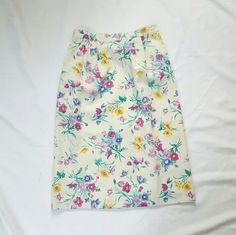 """Vintage High Waisted Floral Skirt This beautiful vintage skirt is unique and quite lovely ! It sits up higher in the waist and flows down straight. There are two front pockets and there's is a button up slit in the back. Skirt is fully lined. The waist has a little bit of a stretch. Length is about 28"""", waist is about 13.5"""". Great vintage condition without any stains, rips, or visable signs of wear ! Vintage Skirts A-Line or Full"""