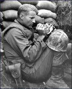 "The little kitten ""crept out from beneath a wrecked"" tank. The U.S. Marine soldier offered water to it. Tarawa, 1943."