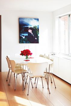 All white modern dining room table and chairs accented with wall art and red roses.