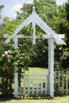 A gated arbor entrance into a spacious green lawn. Vertical shot. Stock Photo