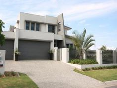 Front facade design in grey and white utilising screening concrete rendered fencing and adding an angled concrete feature to the front of the home