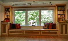 Custom cabinets, window seat and s-curved track light contemporary living room