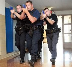 University of Massachusetts police officers Chris Kennedy, Tim Griffin and James Sullivan, from left, move in formation through a hallway in Dickinson Hall during tactical training Sunday