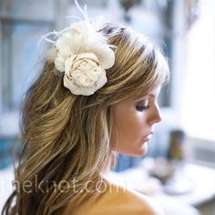 Jennifer removed a couple of flowers from her gown, embellished them with cream and white feathers and then attached them to a comb that she wore in her hair.