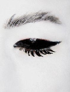 Glossy black eye makeup & painted white skin; dark fashion editorial inspiration