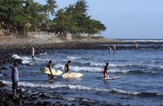 Local surfers head out to catch Medewi Beach's waves. - Paul Kennedy/Getty Images