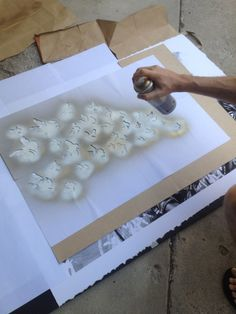 """Art in action.  A picture of us using a stencil and spray paint on a giclee print called """"Kamp Monarch"""".  Available in our store."""