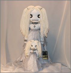 This tattered rag doll is completely hand stitched, stands 22 inches tall, has vintage button eyes, and yarn hair.   She is wearing a white chiffon and silver web lace dress, white panties, white fishnet stockings & white leather shoes.  Her accessories consist a grey leather rhinestone studded choker with a pewter skull, a pewter ghost necklace, a leather wrist cuff with a pewter pentagram, a silver charm bracelet with a pewter ankh, and white skull beads in her hair.  Her hand stitched…