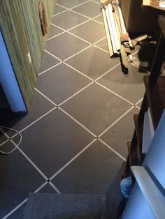 Painted cement floor. Light grey then taped out full length with painters tape. 2' apart then full length the other way 2' apart. Paint with dark grey. Let dry and removed tape. Last of all I made a small square cutout the size of the cross points and spray painted with gloss black to look like small glass tile.