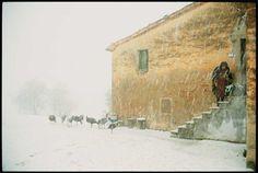 Eine alte Bäuerin im Winter an ihrem Hof in den Marken, Italien