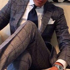グレーのチェック柄スーツに白チーフ、ネイビータイを合わせた着こなし