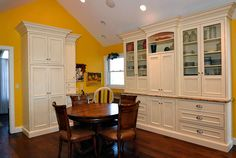 Eat-in section of kitchen with white cabinets with glass doors to display glassware.
