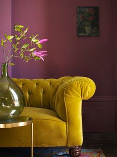 Mustard yellow velvet sofa, vintage green glass vase, pink walls