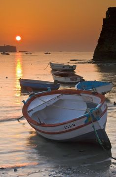 Photo of wooden fishing boats during sunset in the city of Cadiz, Spain.