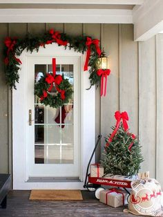 Crimson ribbons and bows take center stage on this charming front porch, accentuating the evergreen tree, garland, and wreath. A red wagon along with a graphic burlap sack and boxes wrapped in brown kraft paper welcome the holiday season. /