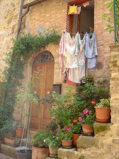 A typical doorway in the lovely town of Pienza, #Italy: flowers, laundry, ancient grey stone and brick.