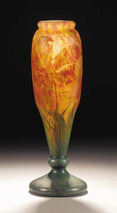DAUM CAMEO GLASS VASE - the frosted grey glass internally mottled with orange, yellow and green towards the baserim, overlaid in green, orange and yellow, etched and carved with floral and foliate decoration, cameo mark Daum Nancy France with a cross of Lorraine -- 41.5cm. high.