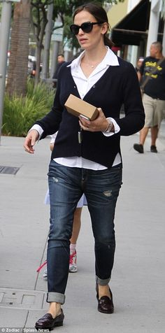 Smart meets casual: The mother-of-three looked great in a white shirt and navy blue cardigan with jeans