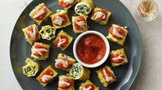 Bite-sized spinach lasagna roll-ups served with pizza sauce for dipping.