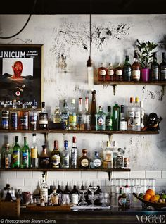 Rustic timber shelving at Sydney laneway bar Bulletin Place displays the bar's premium range of spirits, while old-school greengrocer's scales hold a supply of fresh fruit ripe for cocktails. From 'Special Bulletin' a story on page 54 of Vogue Living April 2013. Photograph by Sharyn Cairns.