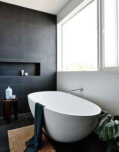 Joli contraste en noir et blanc, baignoire îlot ovale, niche | Black and white bathroom, oval bath tub, niche | Alphington House #salledebain