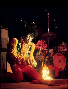 Jimi Hendrix sets his guitar aflame in a kind of ritual scarifice. Rock n Roll Burlesque....
